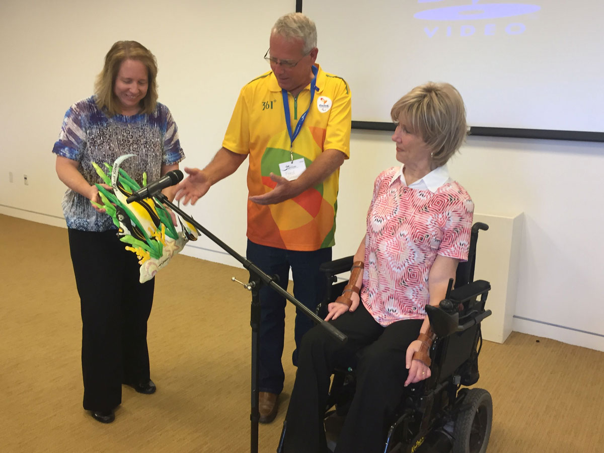 Dr. Fred Sorrells presents a gift of art, created by Francillon Chery, to Joni Eareckson Tada.